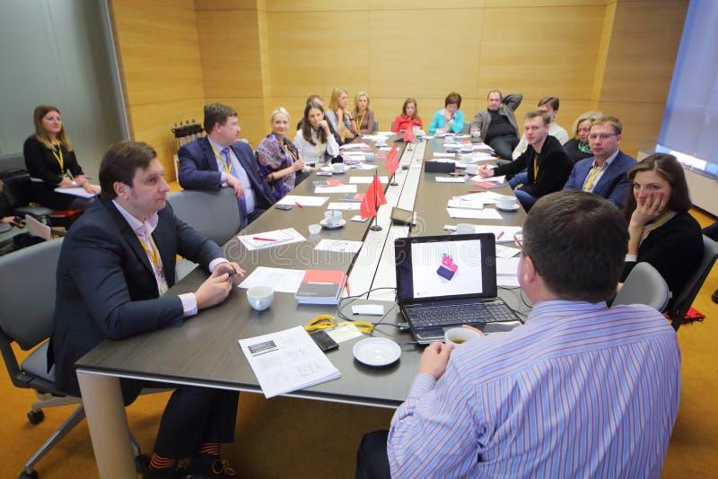Os membros na tabela que debatem no negócio tomam o café da manhã imagem de stock