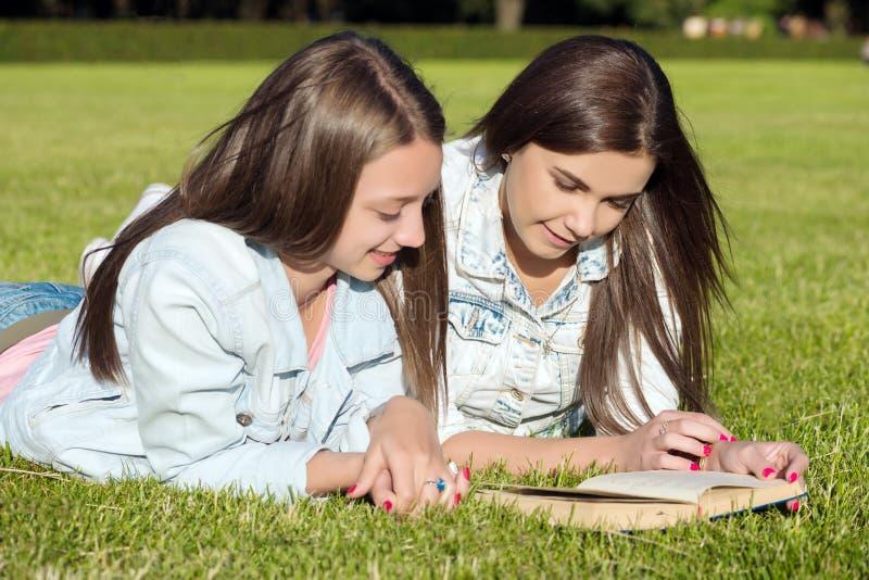 os Menina-estudantes no gramado e leem o livro de texto fotografia de stock royalty free