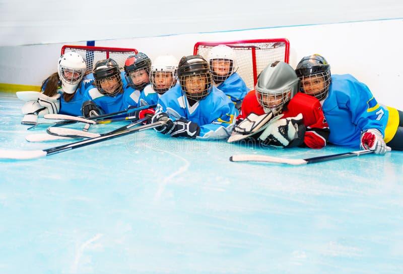 Os meninos alegres e as meninas que colocam no hóquei em gelo rink imagens de stock