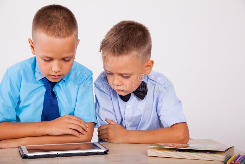 Os meninos aprendem a tabuleta do Internet das lições fotografia de stock royalty free