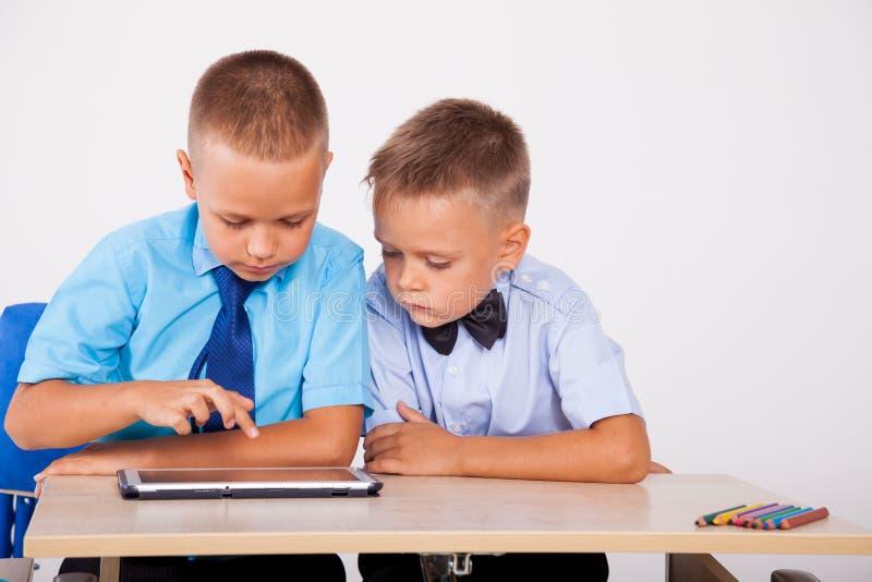 Os meninos aprendem a tabuleta do Internet das lições foto de stock royalty free