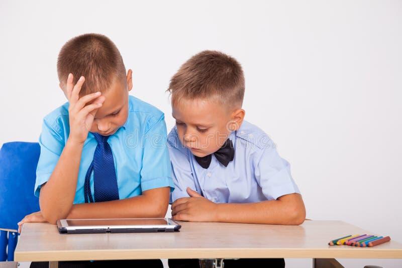 Os meninos aprendem a tabuleta do Internet das lições fotos de stock royalty free