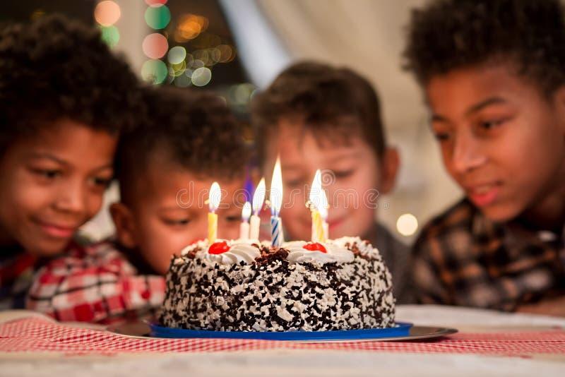 Os meninos de sorriso aproximam o bolo de aniversário imagem de stock royalty free