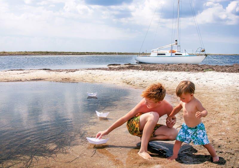 Os meninos estão na praia. imagem de stock