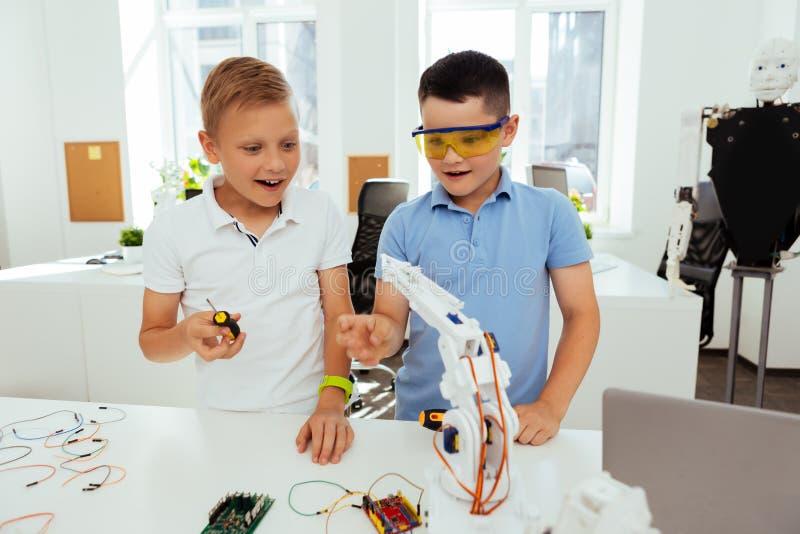 Os meninos felizes alegres que trabalham em sua ciência projetam-se fotos de stock royalty free