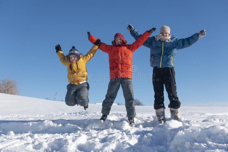 Os meninos felizes saltam no inverno fora fotos de stock royalty free