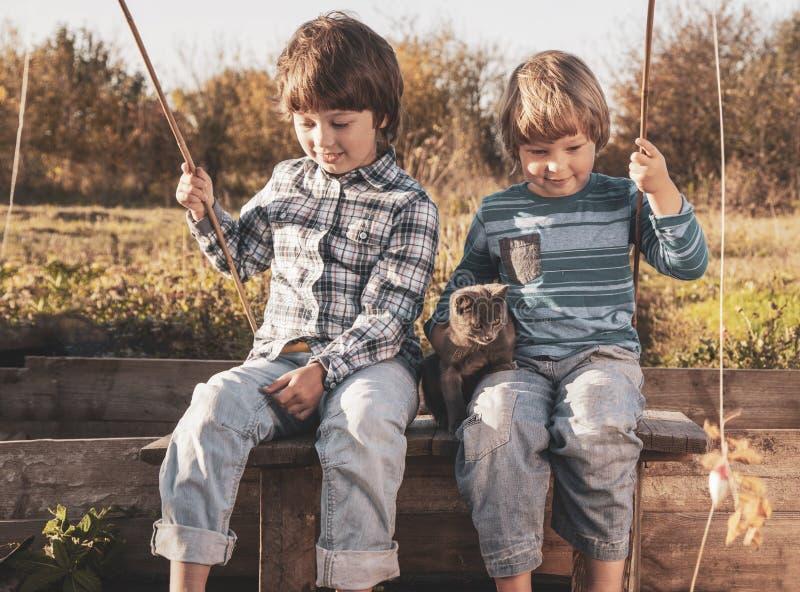 Os meninos felizes vão pescar no rio, duas crianças do fisher com uma vara de pesca na costa do lago fotografia de stock