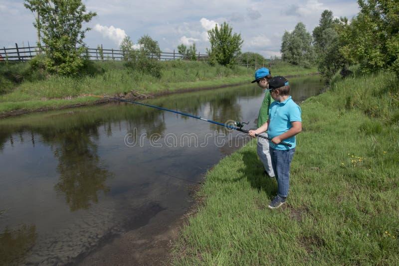 Os meninos felizes v?o pescar no rio, duas crian?as do pescador com uma vara de pesca na costa do lago fotografia de stock royalty free