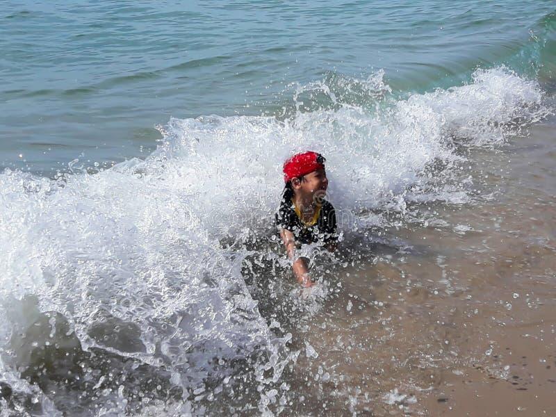 Os meninos jogados na praia do mar imagens de stock