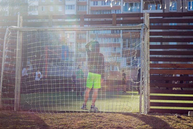 Os meninos jogam no pátio em um campo de futebol especialmente equipado no fundo dos prédios de apartamentos imagens de stock