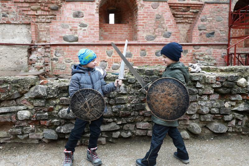 Os meninos lutam com espadas imagens de stock