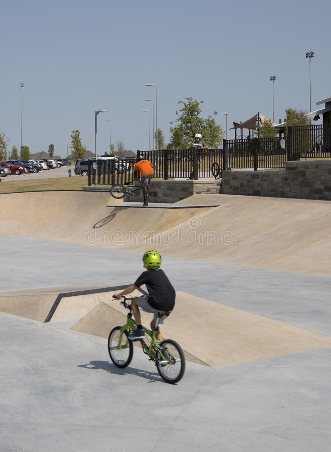 Os meninos montam a bicicleta no parque Frisco Texas do patim fotografia de stock royalty free