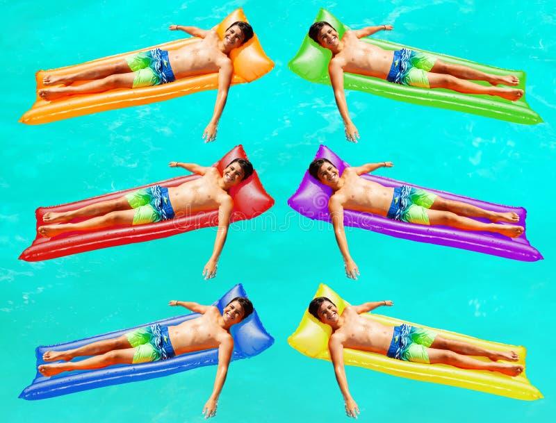 Os meninos nadam em matrasses diferentes da cor na água imagem de stock