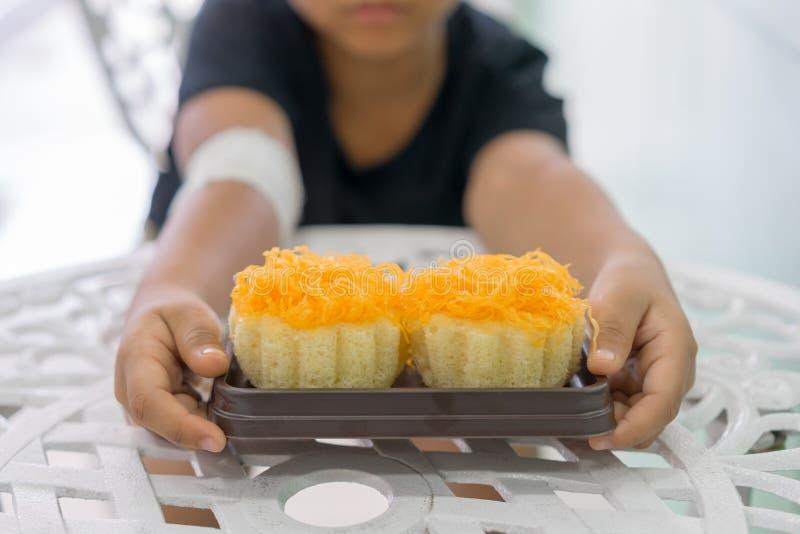 Os meninos nas mãos feridas guardam bolos de uma linha da gema do ouro foto de stock