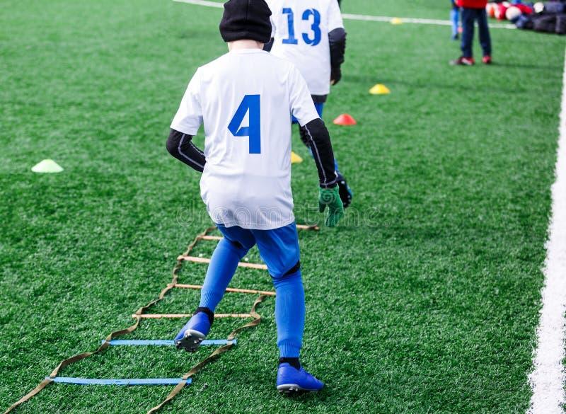 Os meninos no formulário branco e azul do esporte do futebol fazem exercícios no campo verde Futebol para crianças, estilo de vid fotos de stock