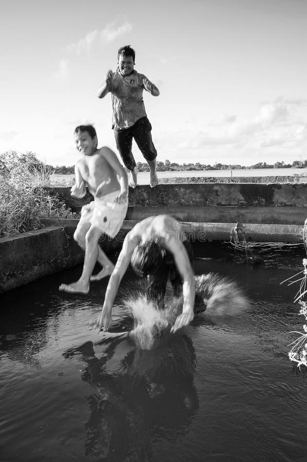 Os meninos novos do campo saltam e nadada no canal Setiu da irrigação do campo de almofada, Terengganu, Malásia o 5 de maio de 20 imagens de stock