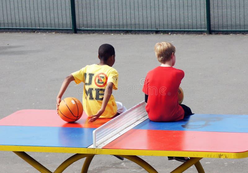 Os meninos novos sentam-se em uma tabela do tênis de mesa imagem de stock royalty free