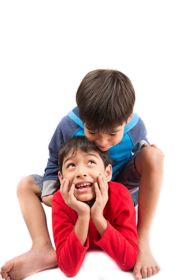 Os meninos pequenos do irmão sentam-se e jogam-se junto no fundo branco imagens de stock