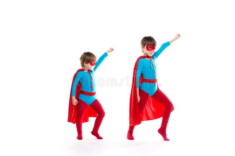 Os meninos são vestidos acima como de um super-herói e de apontar acima com uma máscara e um casaco fotos de stock royalty free