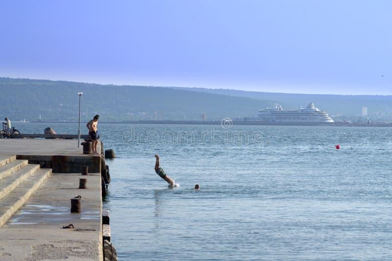 Os meninos saltam no mar fotografia de stock royalty free