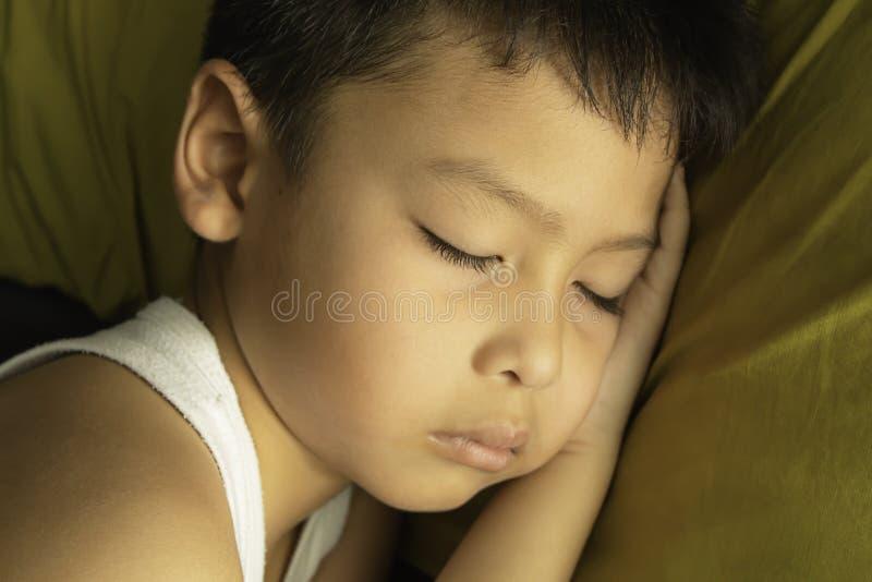 Os meninos vestem as camisas brancas dormem em um verde do descanso fotos de stock