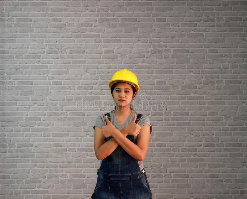 Os mercadorias da mulher do técnico amarelam o capacete com posição cinzenta do vestido do avental das calças de brim do t-shirt  foto de stock