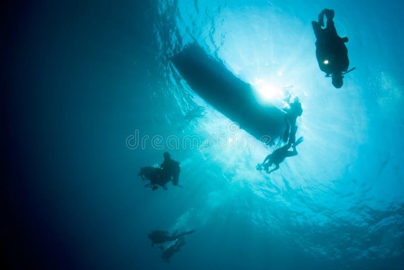 Os mergulhadores de mergulhador descem nas profundidades do Oceano Pacífico tropical fotografia de stock