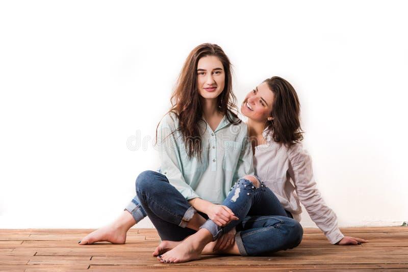 Os mesmos pares felizes novos do sexo no fundo branco foto de stock