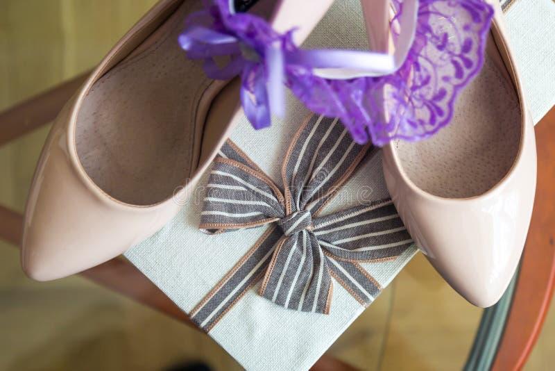Os met een gift en op de achtergrond een purpere kouseband op de bruid` s schoenen stock foto's