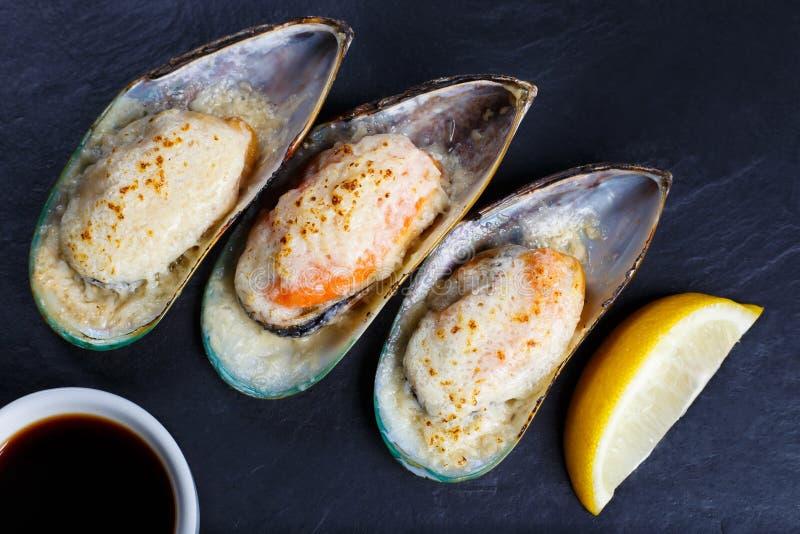 Os mexilhões cozidos do marisco com molho e limão de soja serviram no preto fotos de stock royalty free
