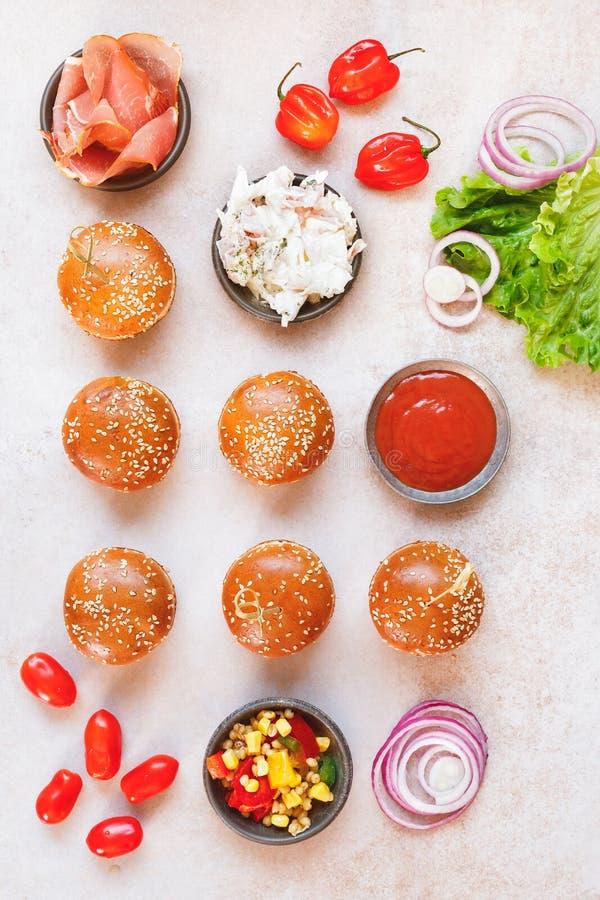 Os mini bolos do hamburguer cobriram com sementes de sésamo e vários enchimentos fotografia de stock