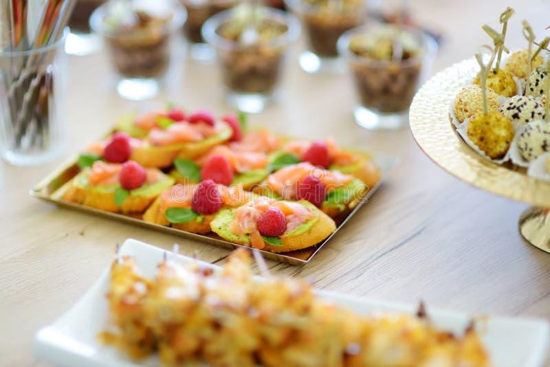 Os mini bruschettas deliciosos dos salmões e da framboesa serviram em um partido ou em um copo de água imagem de stock