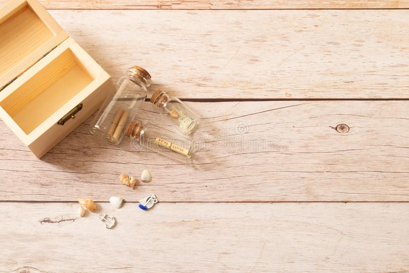 Os mini vidros de garrafa enchem-se com o rolo de papéis pequeno e a caixa de madeira decora com os búzios espirais minúsculos imagens de stock royalty free