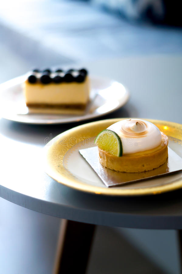 Os mirtilos endurecem e bolos do limão em uma placa do vintage fotos de stock royalty free