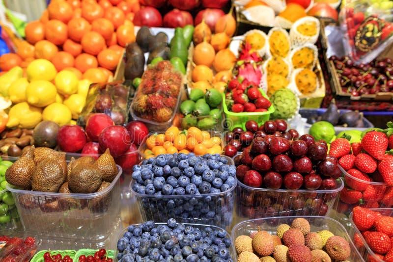 Os mirtilos, frutos da serpente, cerejas, cal, romã, morangos, ameixas, limão, abacates, manga estão no mercado para a venda imagens de stock royalty free