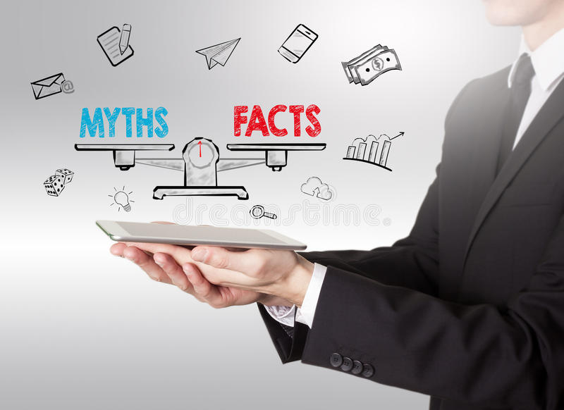 Os mitos contra fatos equilibram, homem novo que guarda um tablet pc fotografia de stock royalty free