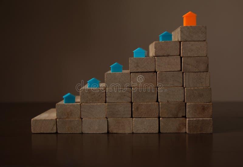 Os modelos crescentes da casa arranjaram em seguido na escadaria de madeira da pilha imagens de stock