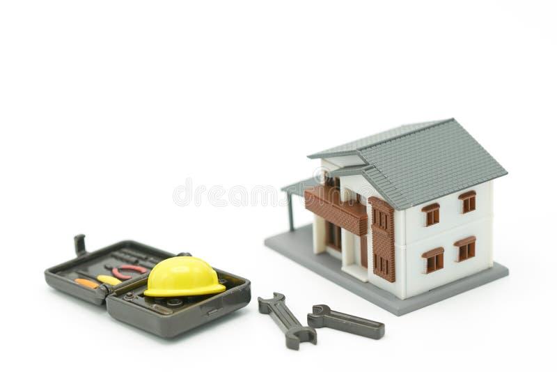 Os modelos da casa e os modelos do equipamento lá são modelos amarelos do capacete da construção Reparo e construção home como o  imagem de stock royalty free