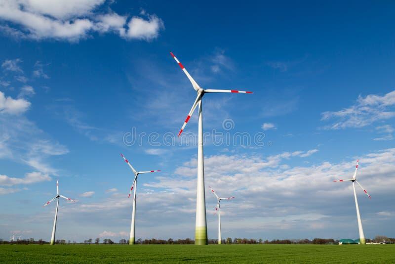 Os moinhos de vento estão em um campo e produzem a eletricidade verde imagem de stock