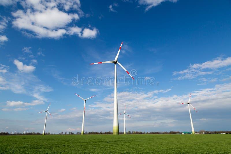Os moinhos de vento estão em um campo e produzem a eletricidade verde fotografia de stock