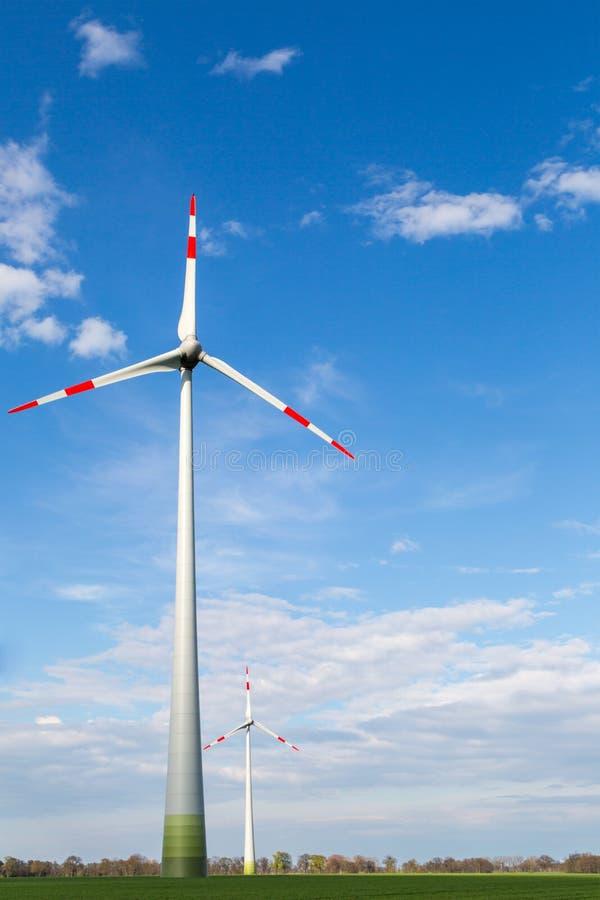 Os moinhos de vento estão em um campo e produzem a eletricidade verde imagens de stock