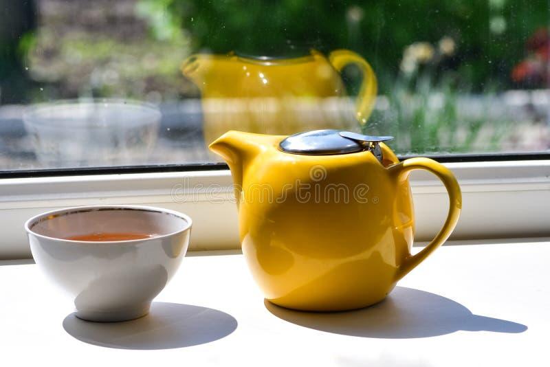 Os momentos simples da vida - um copo com chá verde e bules, estando no peitoril da janela fotos de stock