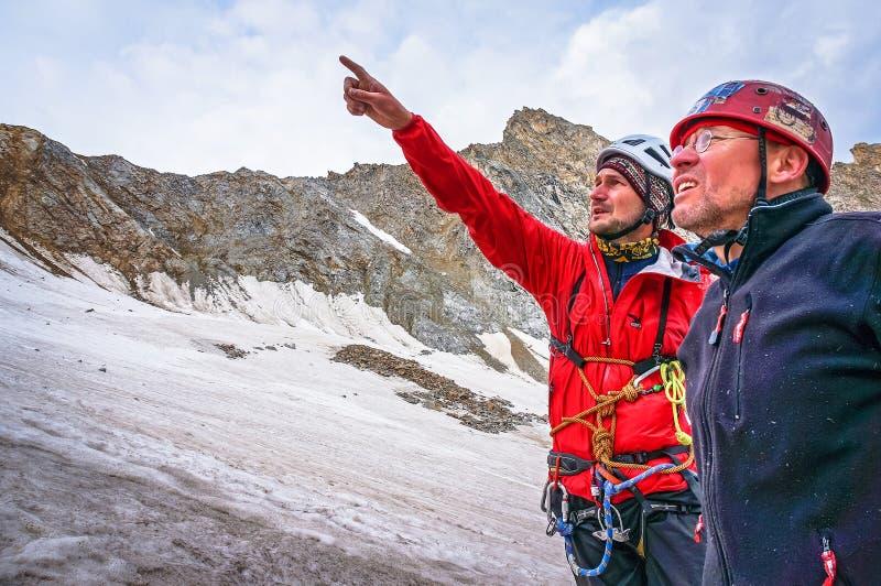 Os montanhistas discutem a elevação das táticas à parte superior imagem de stock