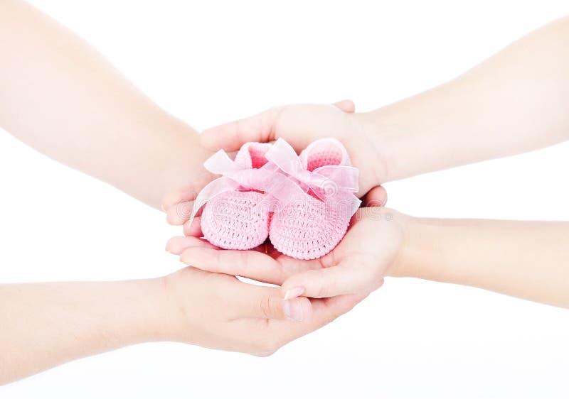 Os montantes recém-nascidos do bebê nas mãos da família, pais acoplam guardar a roupa recém-nascida das crianças fotografia de stock