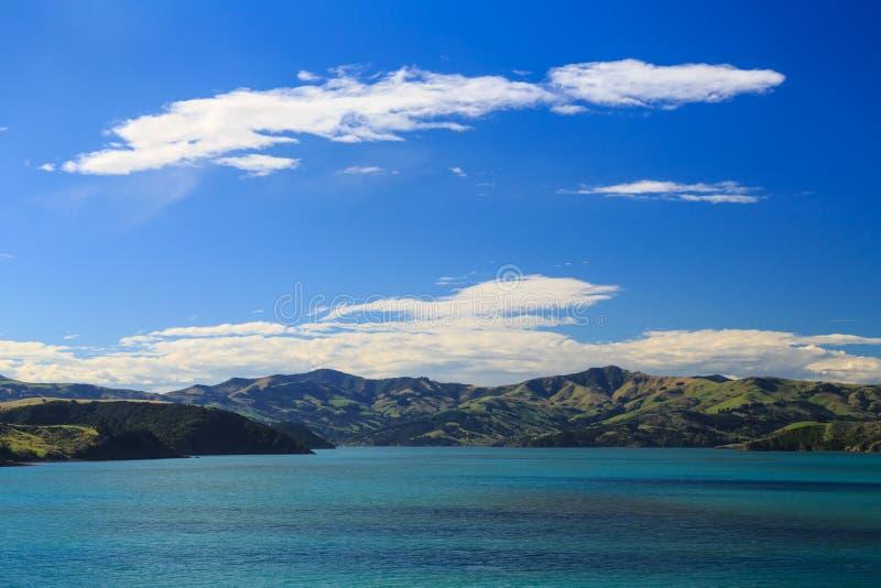 Os montes e as montanhas da península dos bancos, Nova Zelândia, do porto de Akaroa imagem de stock royalty free