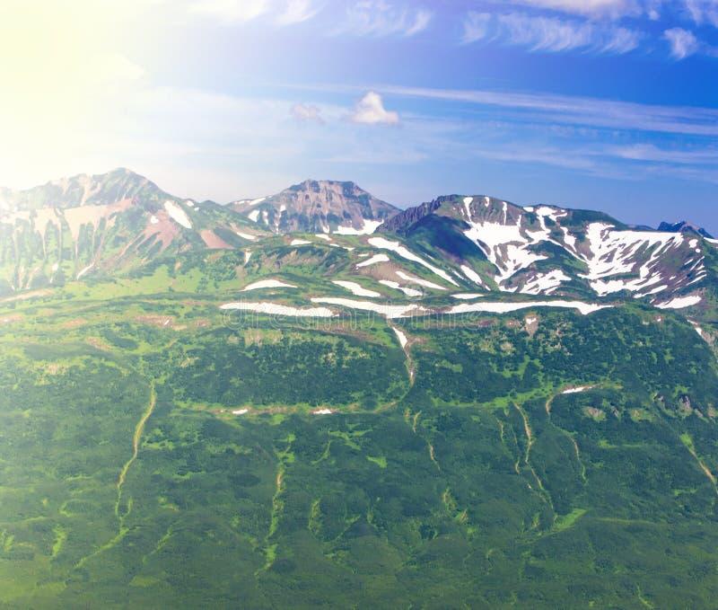 Os montes nevados verdes em um fundo do c?u azul imagens de stock royalty free