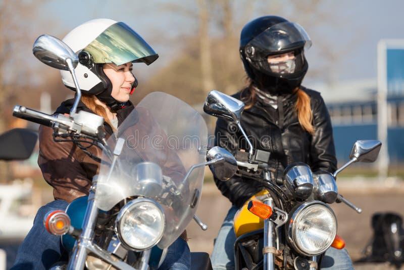 Os motociclistas bonitos das meninas que sentam-se em seus motocicletas, interruptor inversor e rua denominam bicicletas imagem de stock
