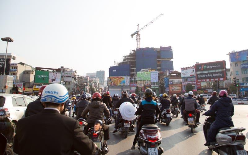 Os motoristas não identificados do velomotor que param na luz vermelha traficam em Hanoi imagem de stock