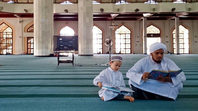 Os muçulmanos relatam um Corão fotografia de stock