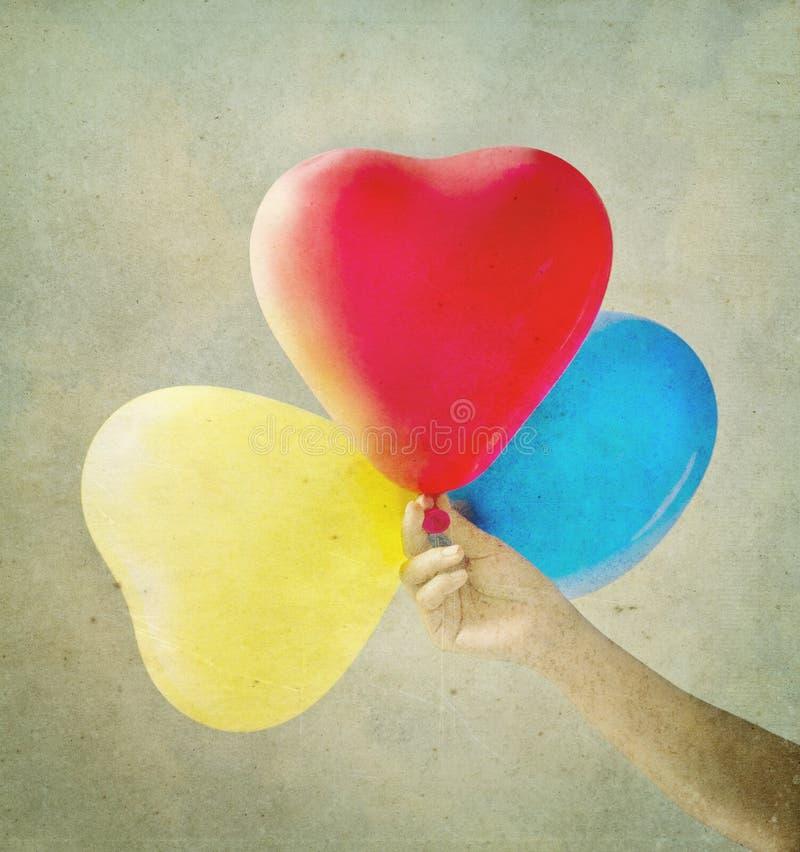 Os multi balões coloridos tonificaram com um fundo retro do vintage imagens de stock royalty free